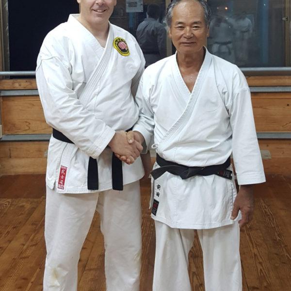 Aiden Thompson receives his black belt from Maeda Sensei in the Hombu dojo, Itoman City, Okinawa, June 2018